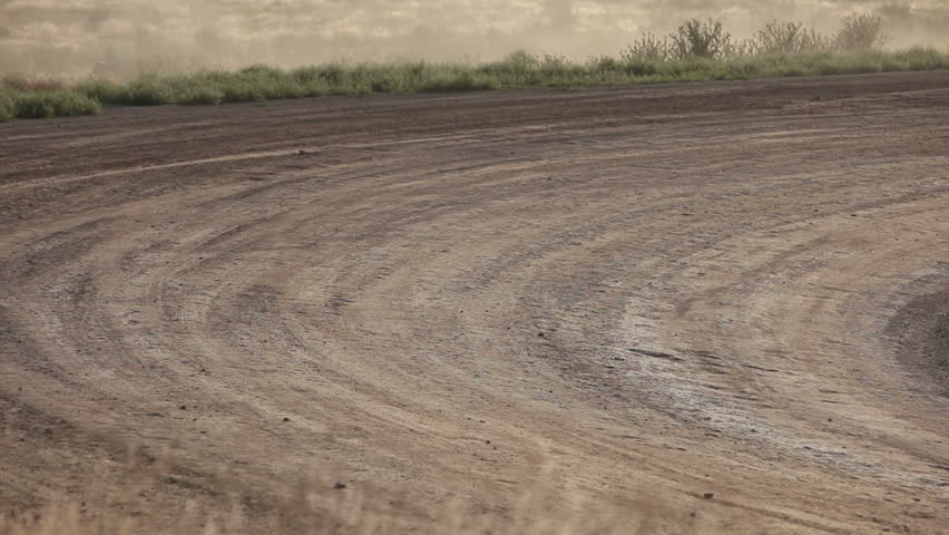 Race cars speed on dirt oval course. Highly modified stock cars driving and racing on a very dirty and dusty track corner. High speed around dusty corner towards view. - HD stock video clip