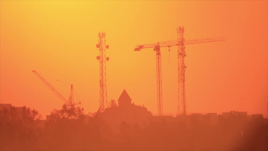 Swallows and swifts silhouettes between towers and cranes at background glowing sky - HD stock footage clip