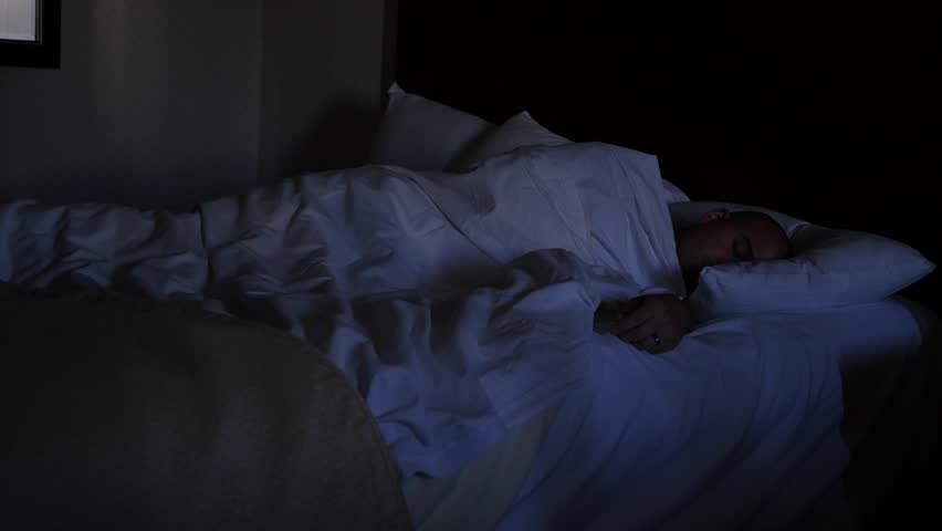 A man is asleep in the hotel bed at night - 4K stock video clip