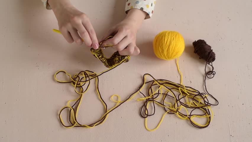 Woman crocheting yellow and brown yarn | Shutterstock HD Video #16211875