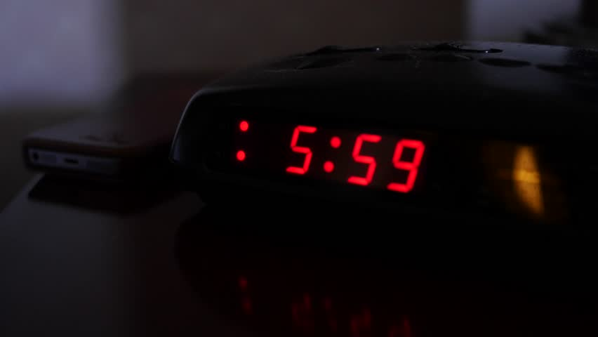 A digital alarm clock turns on at six o'clock and a man turns it off