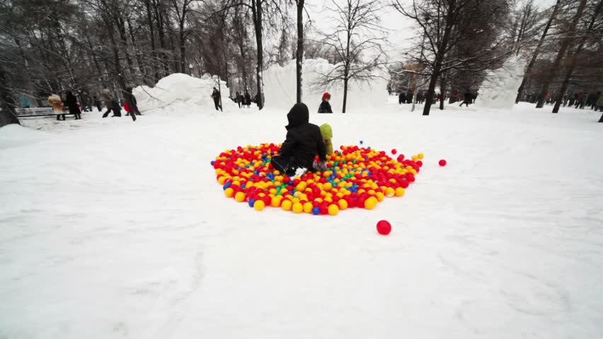 Boy and little girl play in pile of colored balls in park at winter day