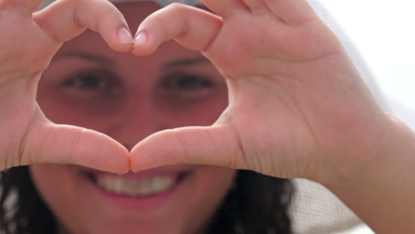 4k Young female with hat outdoors beach vacation hands close up fingers making heart shape welcome symbol posting selfie instant messaging | Shutterstock HD Video #16259575