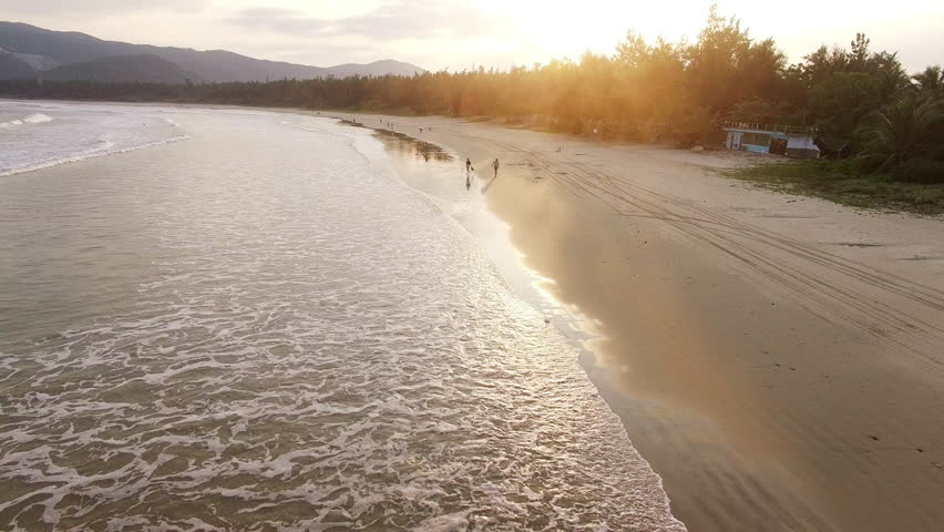 Aerial shot of people walking along the beach