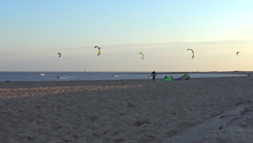 CLACTON-ON-SEA, ESSEX, ENGLAND - 22ND AUGUST 2015: View from the steps leading to a beach of kite surfers in the sea. A man walks past and watches the surfers as they go. - 4K stock footage clip