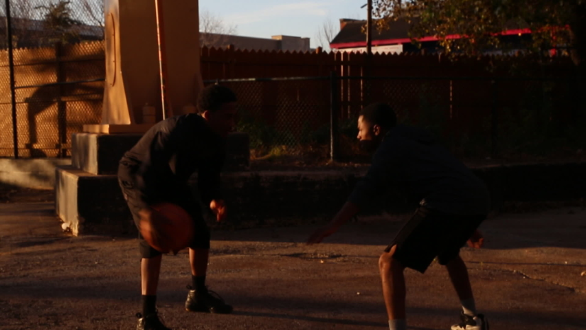 Two young basketball players playing one-on-one on an outdoor court as the sun sets. - Model Released - Clip is HD 1920 x 1080 - HD stock video clip
