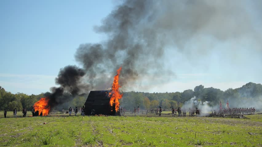 VIRGINIA - OCTOBER 2014 - Reenactment, large-scale, epic American Revolutionary War anniversary recreation -- in the middle of battle. Farm & Farmhouse in flames, burned to the ground by enemy forces