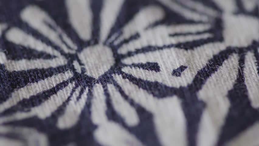 Floral pattern fabric in extreme close up background UHD stock footage, A blue and white flower pattern on a piece of fabric with a rotating camera move.