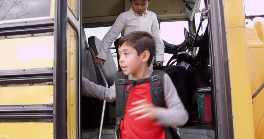 Young elementary school kids getting off a school bus | Shutterstock HD Video #16355857