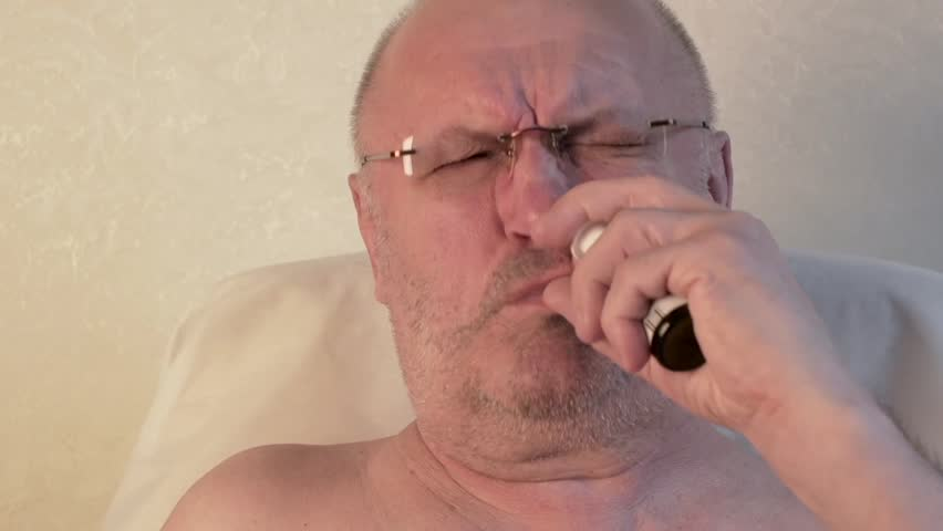 a man with a runny nose sprays a spray in the nose