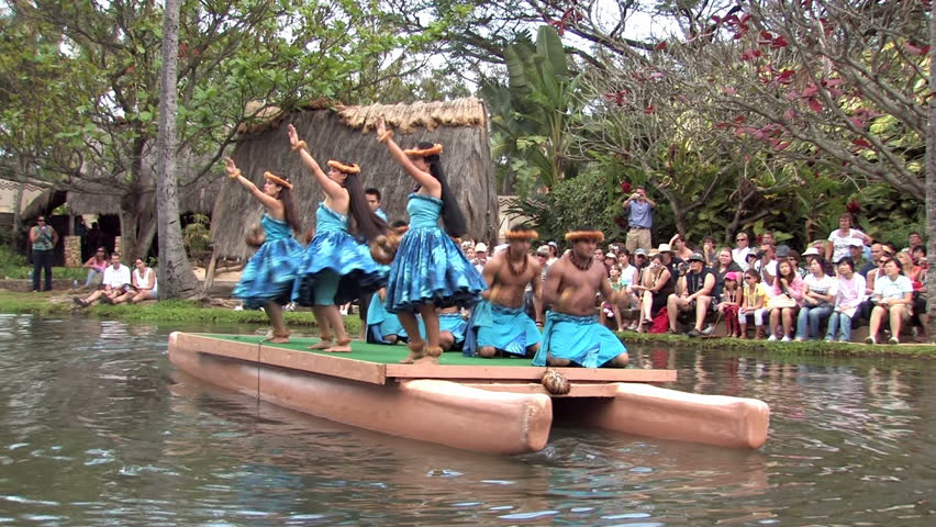 Polynesian Cultural Center in Laie Oahu Hawaii. Canoe show with dancers from Hawaii. Tourists on the main lagoon. Blue skirts on beautiful dancers. Water, lagoon and palm trees. - HD stock footage clip
