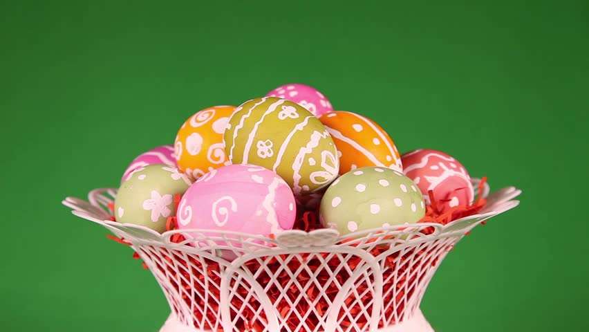 Rotating Easter eggs in basket in front of green background  - HD stock footage clip