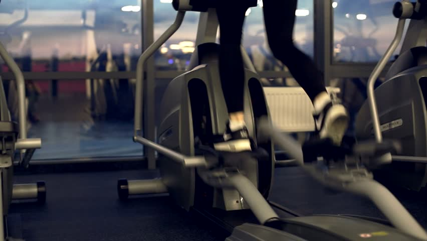 Girl is running on elliptical trainer alone in gym | Shutterstock HD Video #16424653