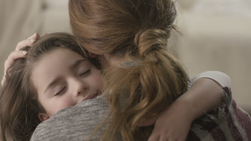 Shutterstock Daughter rushes into mother's arms at home and gives her a big hug. Shot on RED EPIC Cinema Camera in slow motion.