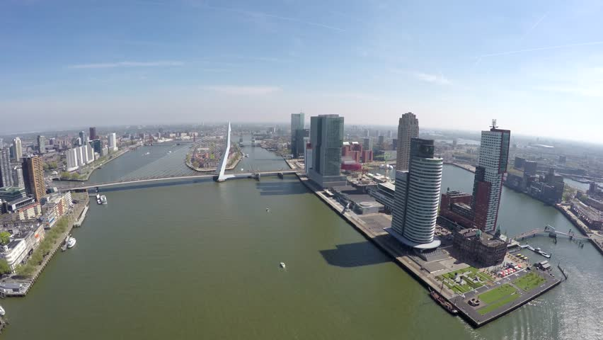 Aerial of Rotterdam city flying closer to Erasmus Bridge Erasmusbrug showing business district right boat sailing past cityscape bird view of city center large city in south of Netherlands Holland 4k #16455361