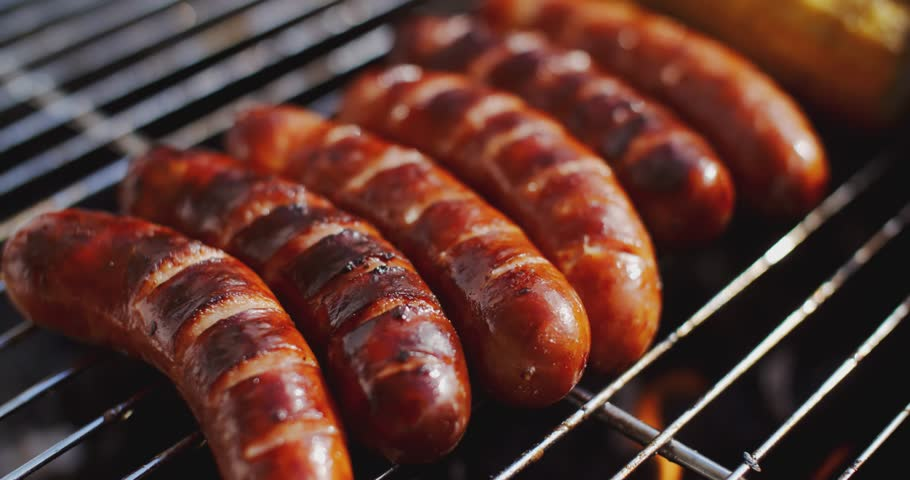 Tasty juicy sausages grilling over a fire