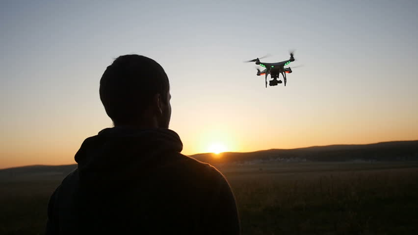 A man controls a drone at sunset | Shutterstock HD Video #16505374