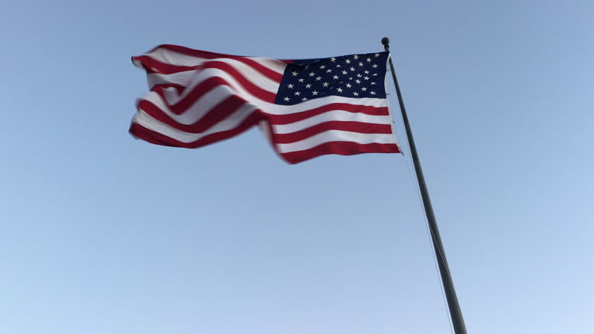 American flag billows and ripples in gentle breeze against a clear blue cloudless sky, low angle moving shot - 4K stock footage clip