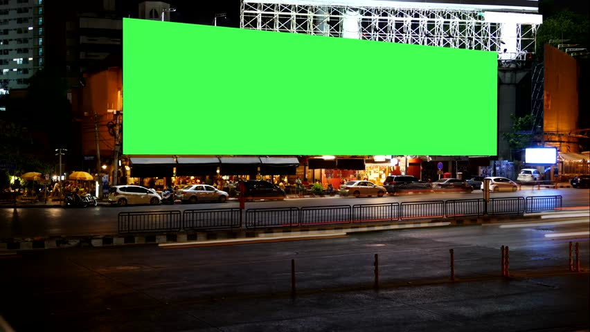 Blank Advertising Billboard green screen beside road with traffic at night, for advertisement, time lapse.