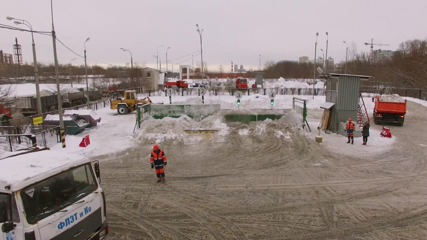 MOSCOW - JAN 20, 2016: People work on snow melting station with trucks at winter day. Aerial view