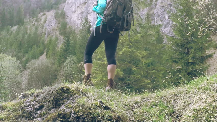 Woman hiking around mountains at spreeng time. - HD stock footage clip