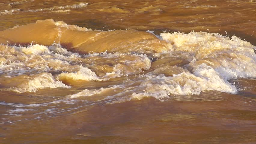 SLOW MOTION: Flash flood muddy river fast flowing. Flood river rushes, river raging. Natural disasters, stormy swollen river. Brown water flow. - HD stock footage clip