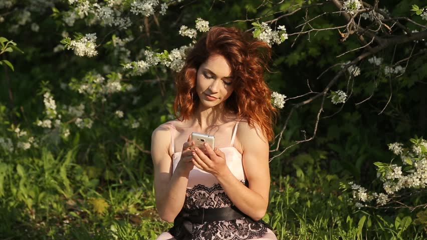 Girl with red hair uses a smartphone - HD stock footage clip