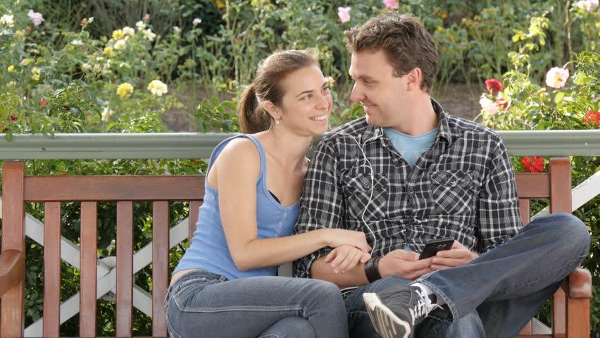 Sharing music headphone romantic young couple on park bench enjoying life - 4K stock video clip