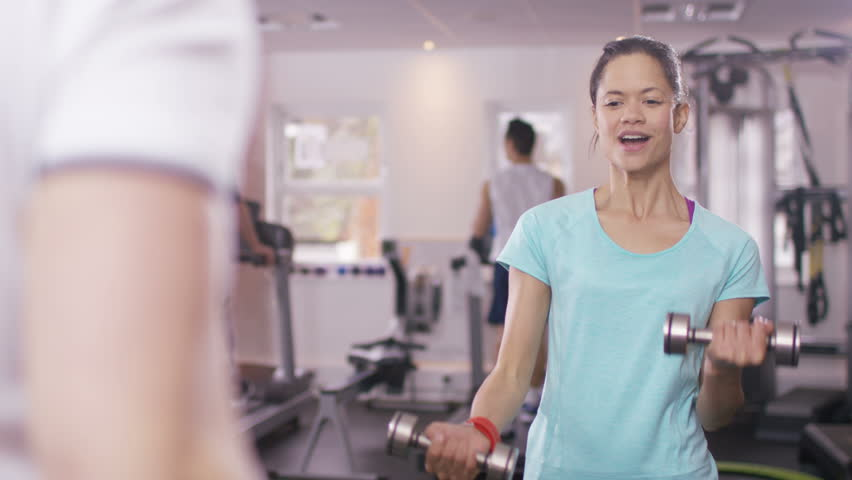 4K Woman working out with personal trainer at the gym. Shot on RED Epic. UK - April, 2016 - 4K stock video clip