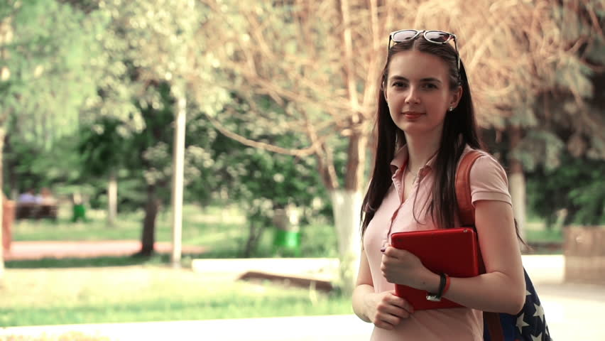 footage young beautiful woman walking in the park and waving at the camera. student a tablet in hands. HD video