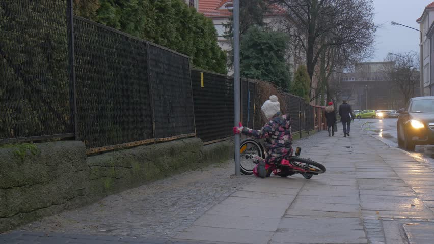 Kid Fell Down of Bicycle, Gets Up, Kid Lames, Walking Back and Crying, Child Was Riding a Bicycle by City Street, Left Her Bicycle, Cars Are Parked Along a Sidewalk, Driven Cars, Walking People , | Shutterstock HD Video #16925341