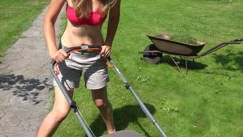 Lady riding as she mows her lawn with her red lawn tractor mower and