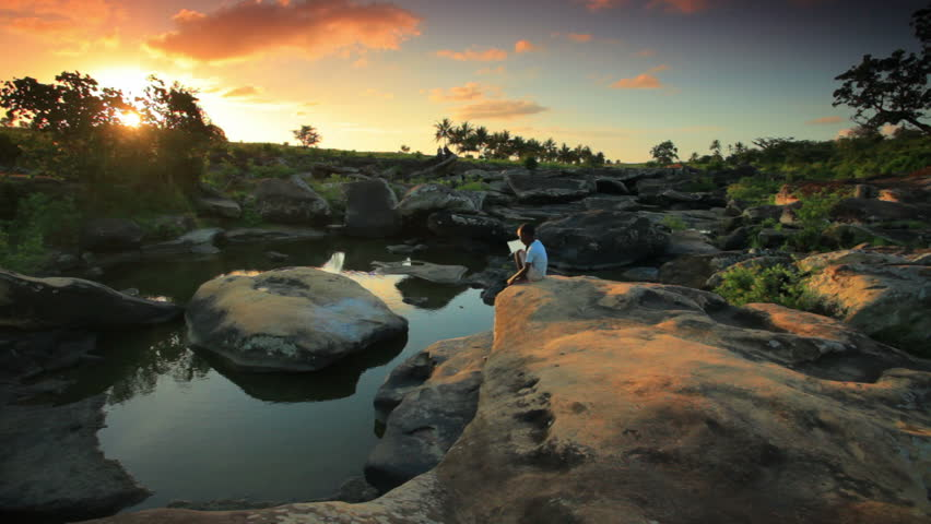 A child sitting on a rock near a village in Kenya two hours north of the African city Mombassa at sunset.