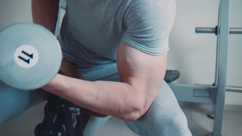 Close-up of unrecognizable sportsman doing dumbbell concentration curl - HD stock footage clip