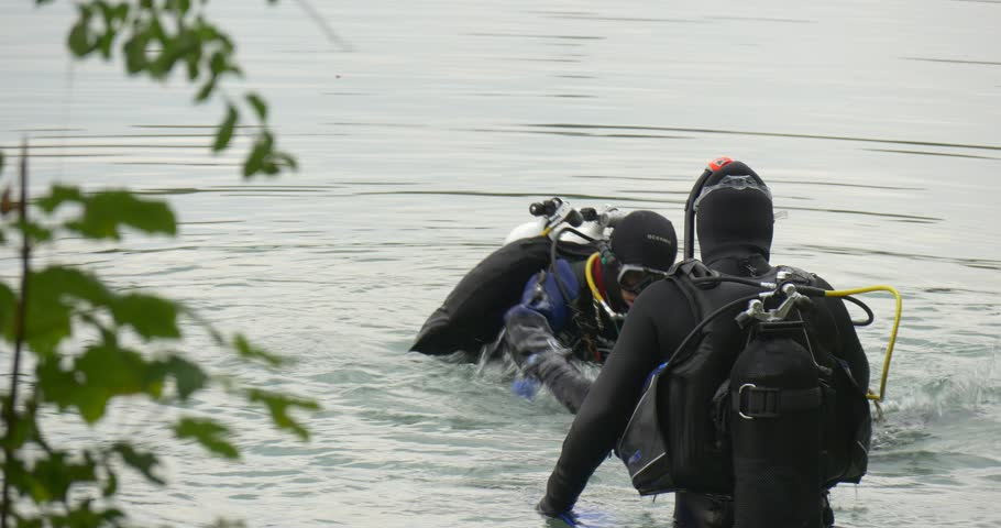 Opole/poland - Sep 23 2015: Three Men Divers in Swimsuits Are Standing in the Water, Checking the Equipment, Holding Blue Flipper, Divers Are Talking, Going to Dive, Finished Diving, Men, Divers, Man - 4K stock video clip