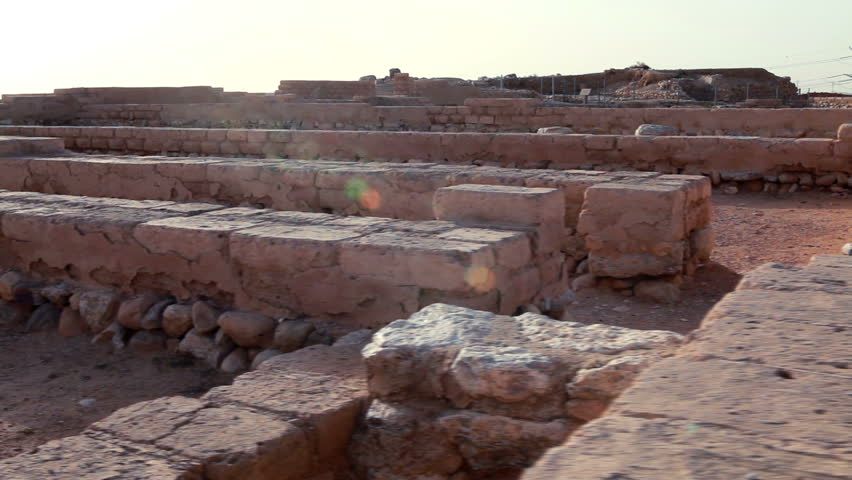 the ruins of the biblical city at Tel Be'er Sheva National Park in Israel.  The shot is facing the evening sun so there are shadows and lens flares. - HD stock video clip
