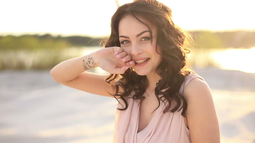Close up of young seductive brunette  woman flirting on  camera and laugh, hair blowing in wind. Sunny beach background at sunset | Shutterstock HD Video #17073679