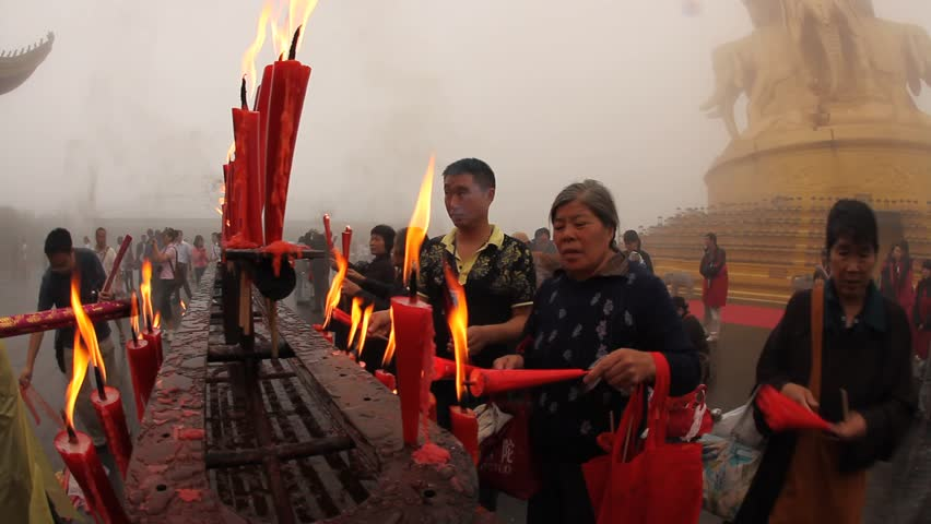 MOUNT EMEI, CHINA - JULY 22, 2009: People light candles and incense outside the Golden Summit Temple on July 22, 2009 on Mount Emei. - HD stock footage clip