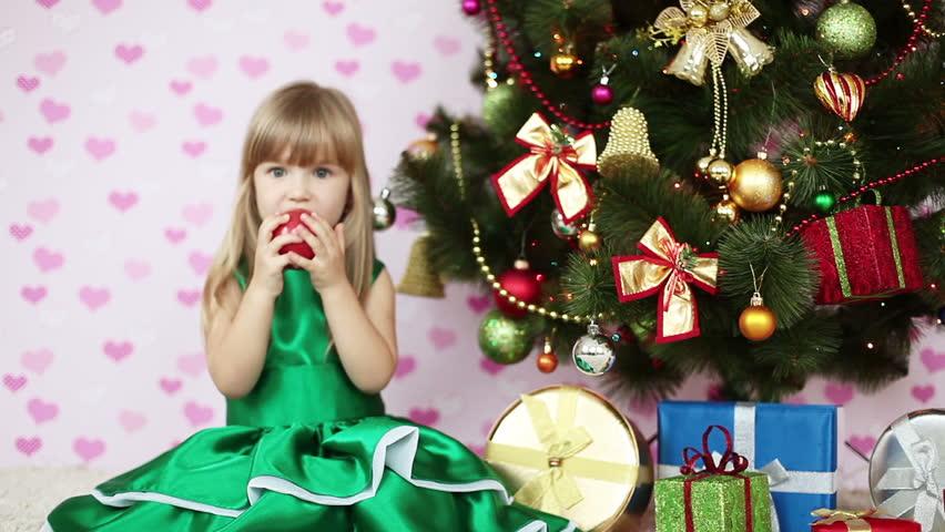 Girl eating an apple near a Christmas tree. She sits on the floor - HD stock footage clip