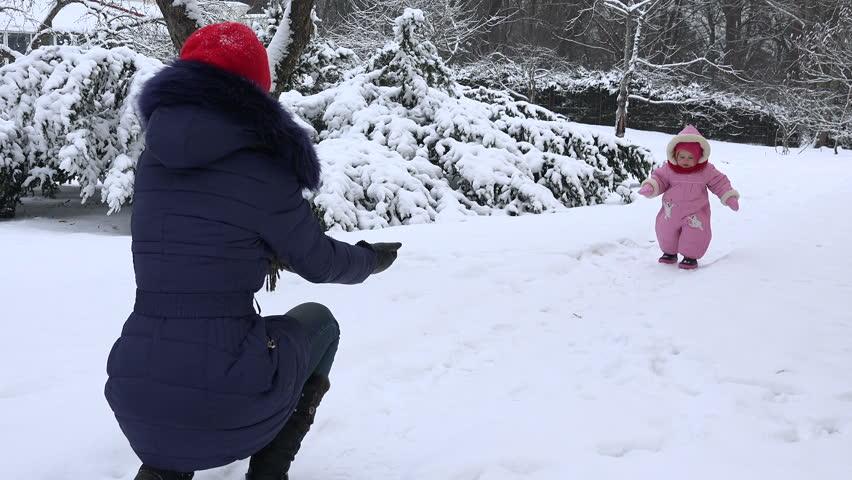 Happy baby girl walk toward mother on snow in winter season. 4K | Shutterstock HD Video #17135500