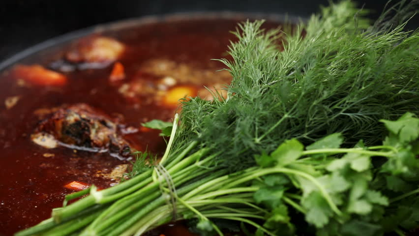 Cooking soup with lamb in a cauldron on a wood stove in the winter. A bunch of dill and parsley added in the cauldron. #17138704