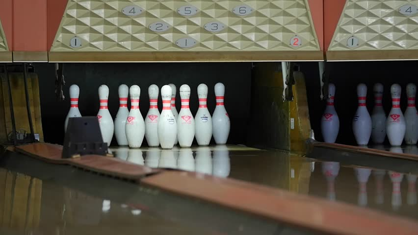A slow motion shot of people bowling in a small town bowling alley