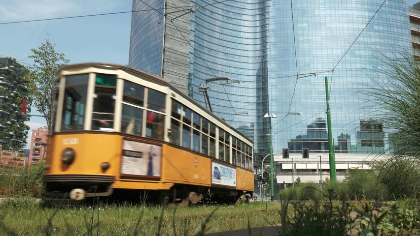 Milan, Italy - circa May 2016: an old tram passes below a skyscraper in the financial district - 4K stock video clip