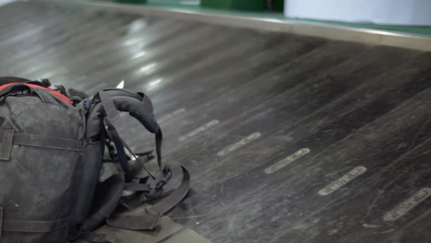 lost single backpack forgotten on an empty modern luggage belt in the airport, baggage claim conveyor, lost luggage