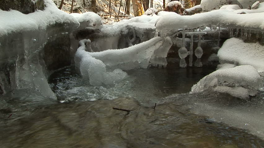 Water current pours into natural pool with ice formations - HD stock footage clip