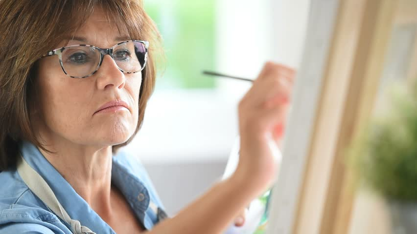 Senior woman painting on canvas - HD stock footage clip
