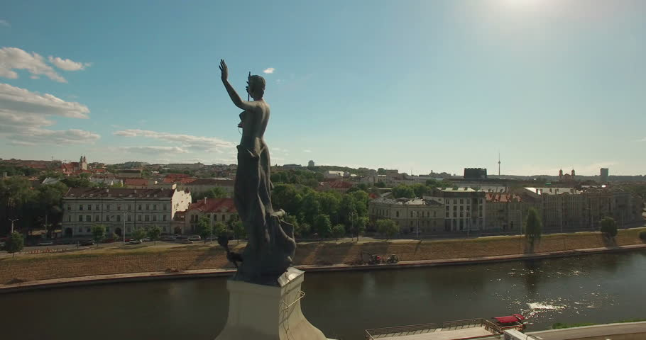 AERIAL. Smooth orbit flight around statue on top of the Electricity building. Old town of Vilnius, Lithuania in the background