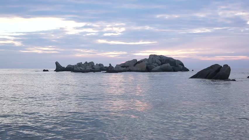 Sunrise moment with sleeping giant shaped rock formation at beautiful beach at Kijal Kemaman Terengganu Malaysia. HD footage. - HD stock footage clip