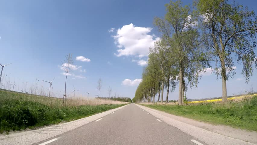 Video footage P.O.V. in 4K of driving in the netherlands in agricultural landscape - 4K stock video clip