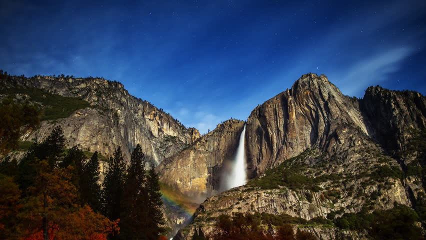 Astrophotography time lapse with tilt down motion of Moonbow (Lunar Rainbow) at Yosemite Falls in Yosemite National Park, California